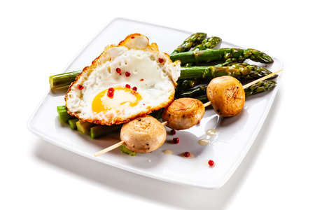 Fried egg with asparagus on white background Banco de Imagens