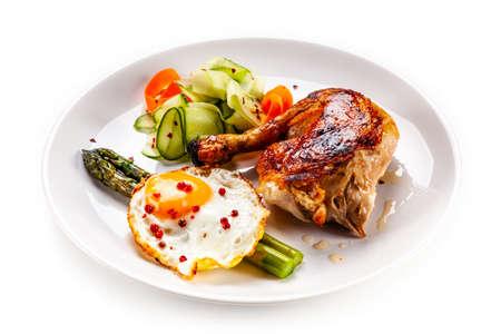 Uovo fritto con asparagi e coscia di pollo su sfondo bianco