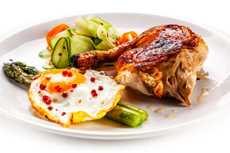 Fried egg with asparagus and chicken legon white background Stock Photo
