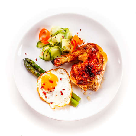 Fried egg with asparagus and chicken legon white background Stock fotó