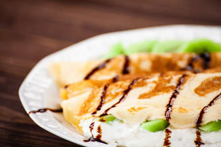 Crepes with kiwi and cream on wooden background Stock fotó
