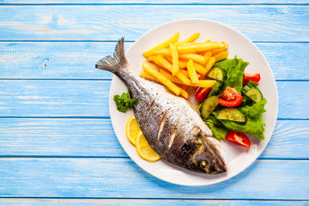Gebratener Fisch mit Pommes frites und Gemüse auf Holzuntergrund