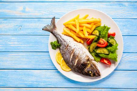 Pesce arrosto con patatine fritte e verdure su fondo di legno