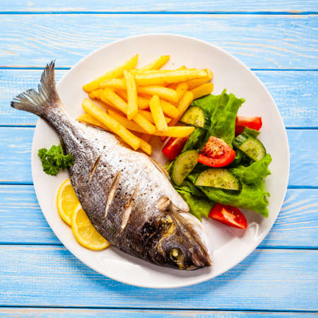 Roast fish with french fries and vegetable on wooden background