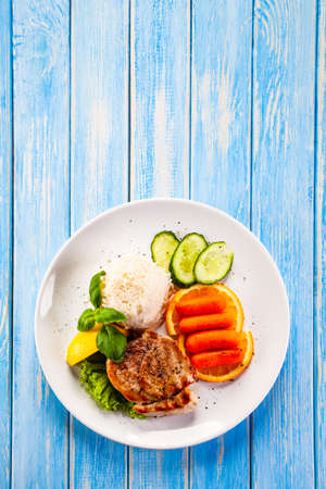 Roast steak with white rice and vegetables on wooden background