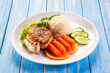 Roast steak with white rice and vegetables on wooden background Reklamní fotografie