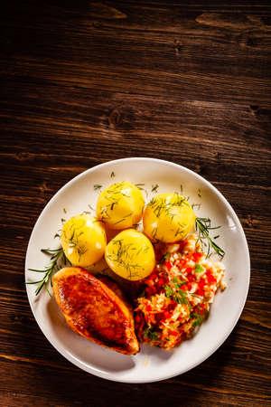 Pollo fritto con patate bollite e verdure su fondo di legno