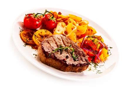 Grilled steak with fried potatoes and vegetables on white background Stock Photo