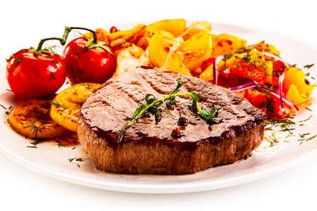 Bistec a la plancha con patatas fritas y verduras sobre fondo blanco. Foto de archivo