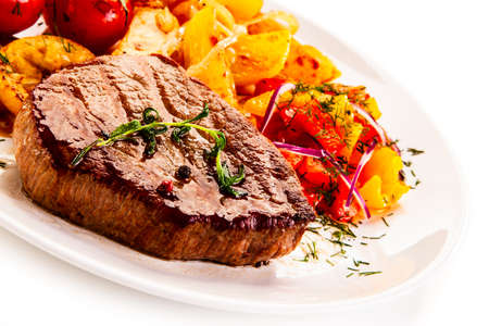 Grilled steak with fried potatoes and vegetables on white background Foto de archivo