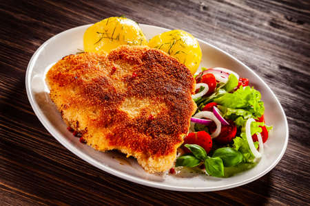 Schnitzel with boiled potatoes on timber background
