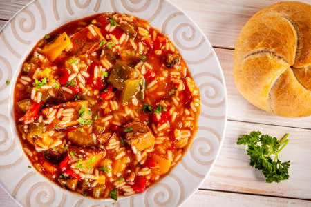 Roast pork meat with rice and vegtables on wooden background