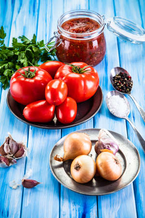 Raw tomatoes and tomato sauce in jar on wooden background