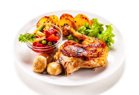 Barbecued chicken leg with chips and vegetables on white background Reklamní fotografie