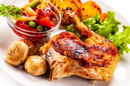 Pierna de pollo asado con patatas fritas y verduras sobre fondo blanco.