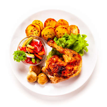 Top view of barbecued chicken leg with chips and vegetables on white background