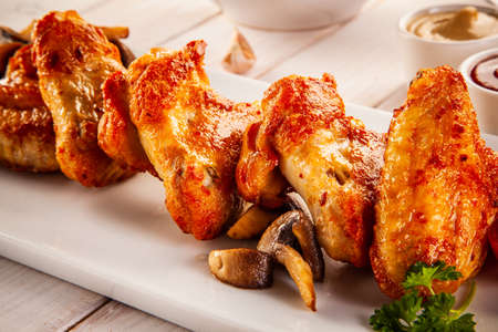 Barbecued chicken wings with french fries and vegetable salad on timber