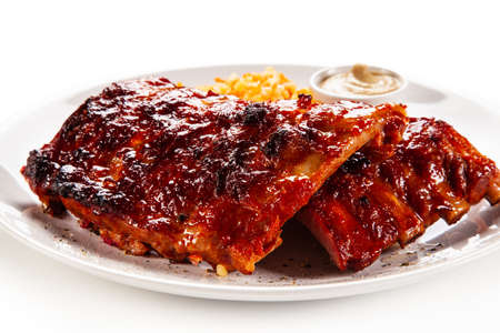 Barbecued ribs and vegetables on white background