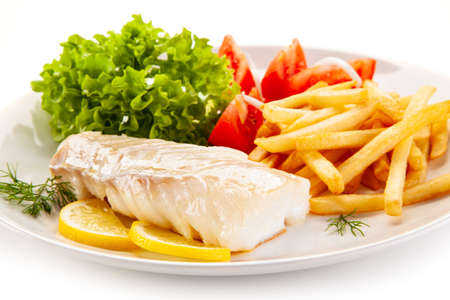 Fish dish - fried cod fillet with vegetables on white background
