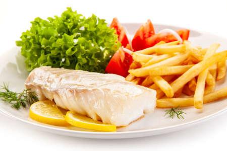 Plato de pescado - Filete de bacalao frito con verduras sobre fondo blanco.