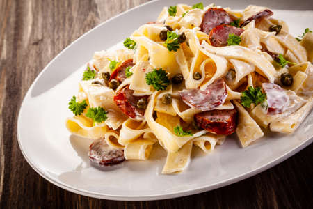 Pasta with cream sauce and sausages on wooden background