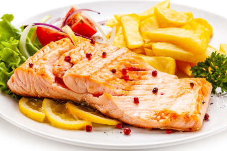 Roast salmon, french fries and vegetables on white background Stock Photo