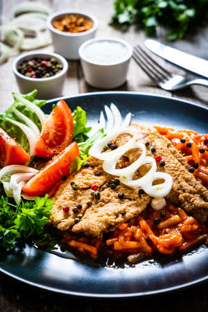 Fish dish - fried fish fillet on vegetable sauce on wooden table Foto de archivo