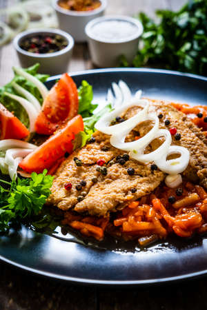 Fish dish - fried fish fillet on vegetable sauce on wooden table