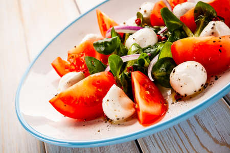 Caprese salad on wooden table