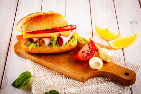 Tasty sandwich with meat and vegetables on wooden table Banco de Imagens