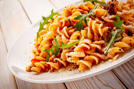Fusilli with sausages and vegetables on wooden table Stock fotó