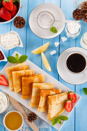 Crepes with strawberries and jam on wooden table