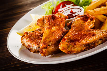 Fried chicken wings with french fries and vegetable salad Banco de Imagens