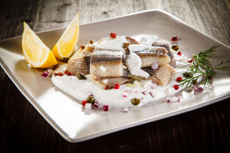 Marinated herring fillets on wooden table