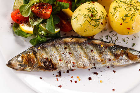 Fish dish - grilled herring with vegetables on white background