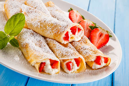 Sweet crepes with fruits on wooden table