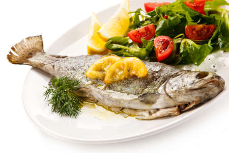 Fish dish - roasted trout with vegetables on white background