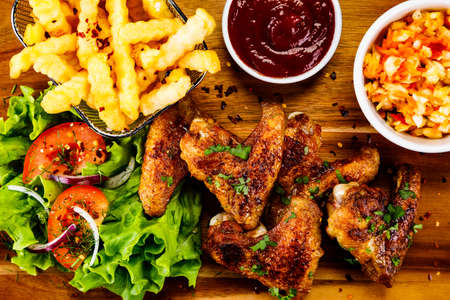 Fried chicken wings with french fries and vegetable salad on wooden board 스톡 콘텐츠