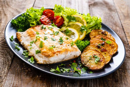 Fish dish - fried cod fillet with potatoes and vegetables on wooden table