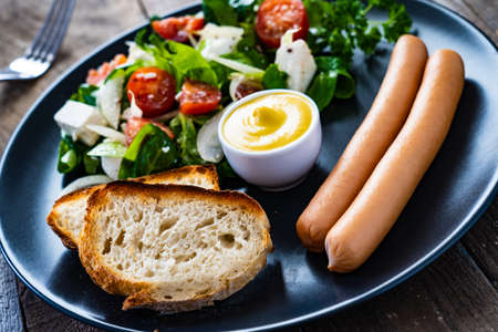Boiled sausages with vegetable salad and toasted bread