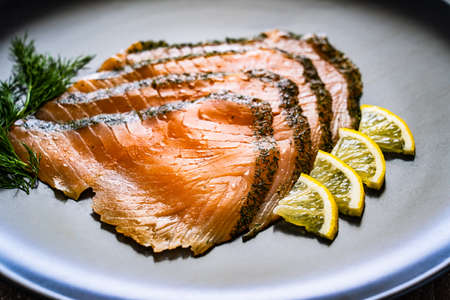 Fresh, raw, cutted salmon on plate on wooden background