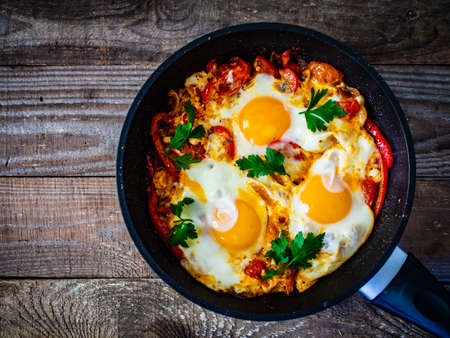 Shakshouka - dish of eggs poached in a sauce of tomatoes, chili peppers, onions