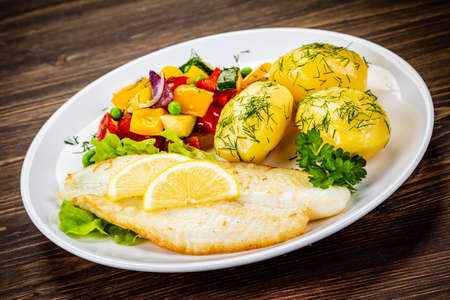 Fish dish - fried fish fillets with boiled potatoes and grilled vegetables