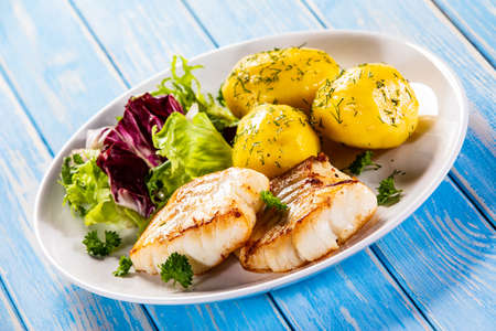 Fried fish with potatoes and vegetable salad on wooden table
