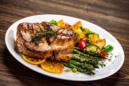 Grilled steak with asparagus and grilled vegetables on wooden table