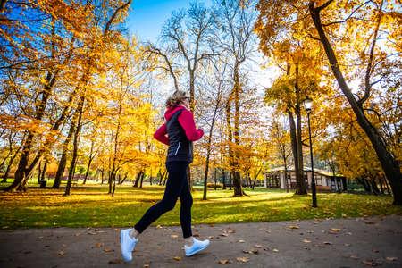 健康的なライフスタイル - 市立公園で走っている女性