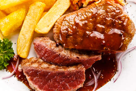 Grilled steak with french fries on white background