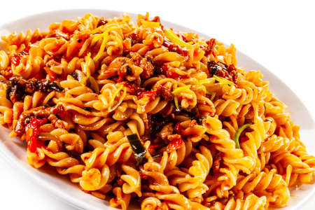 Pasta with tomato sauce and vegetables on white background