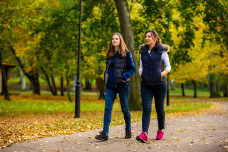Two women walking in city park