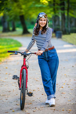 Woman standing with bike in city park